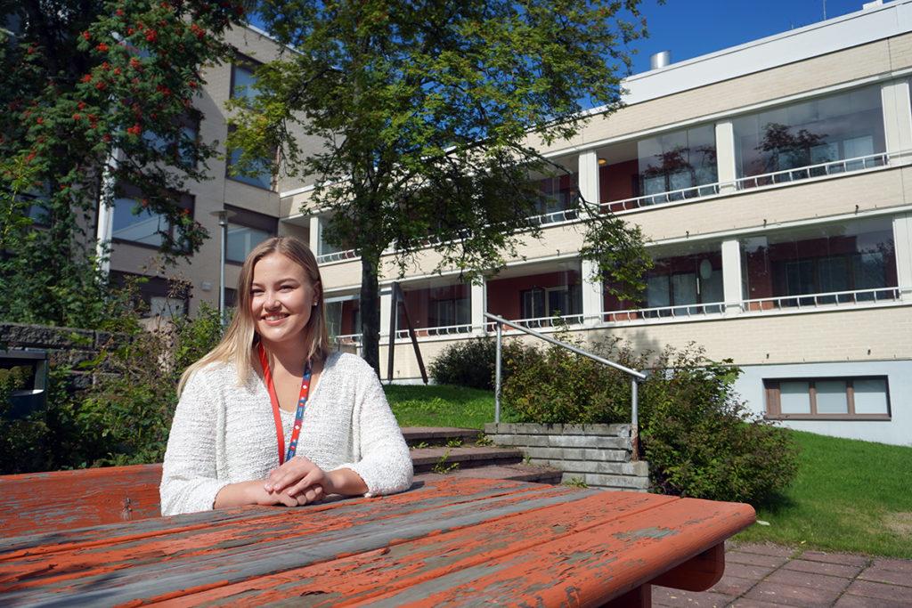 Kesätyöntekijä Laura Salomäki istuu ulkona puistonpöydän ääressä.