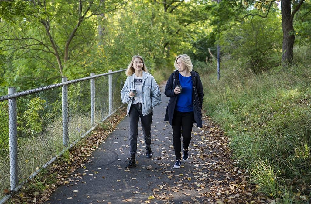 Kaksi naista kävelee polulla. Keskustelussa ehkä foorumi vanhemmille?