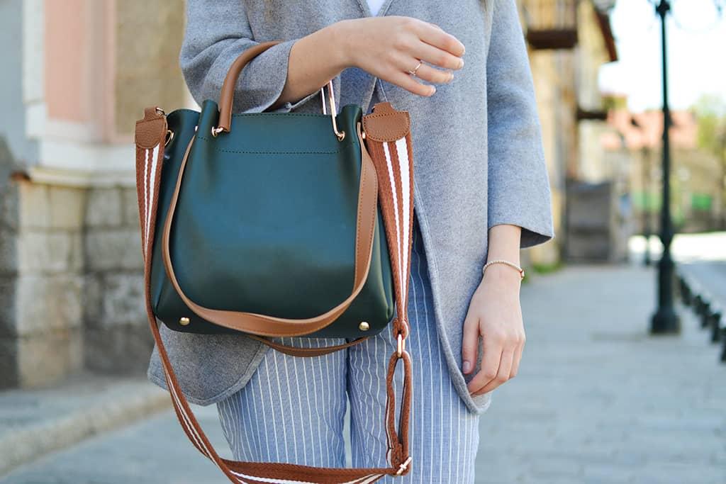 Käsilaukku naisen käsivarrella.
