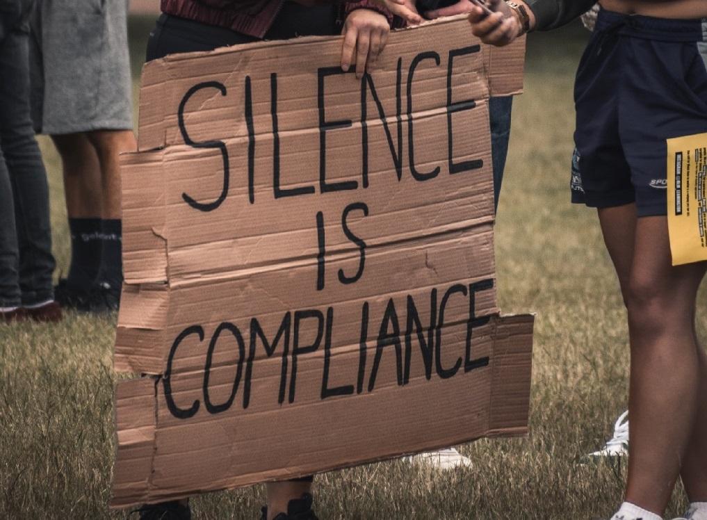 """Pahvikyltti, johon on kirjoitettu tussilla """"Silence is compliance""""."""