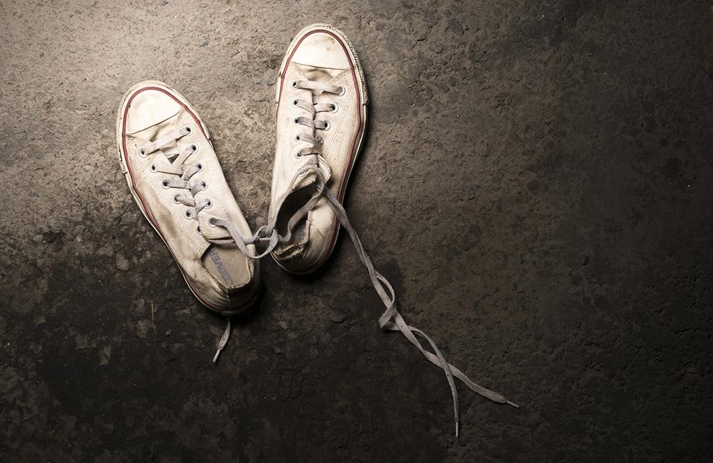 Valkoiset tennarit asfaltilla.