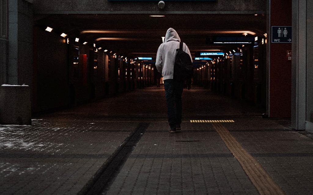 Henkilö kävelee reppu selässä tunneliin.
