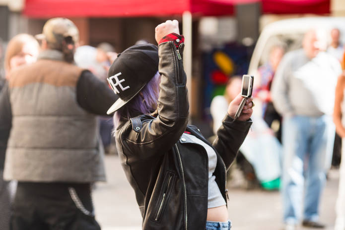 Tyttö tanssii pihalla kännykkä kädessä.