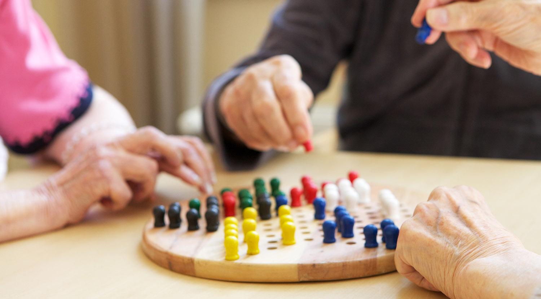 Kolme ihmistä pelaa lautapeliä.