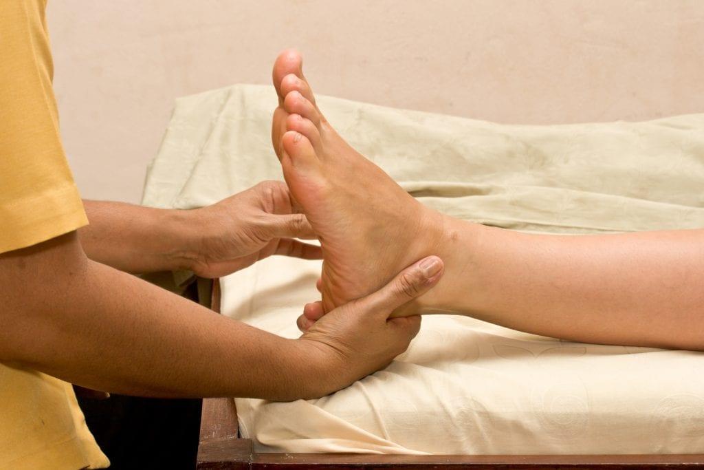 Jalkojenhoitaja hieroo asiakkaan jalkaa.