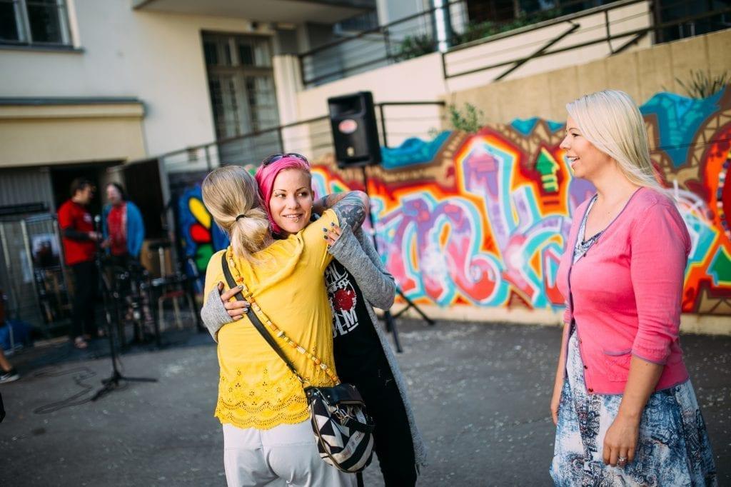 kaksi naista halaa toisiaan, kolmas seisoo heidän vieressään. Takan on värikäs graffiti.