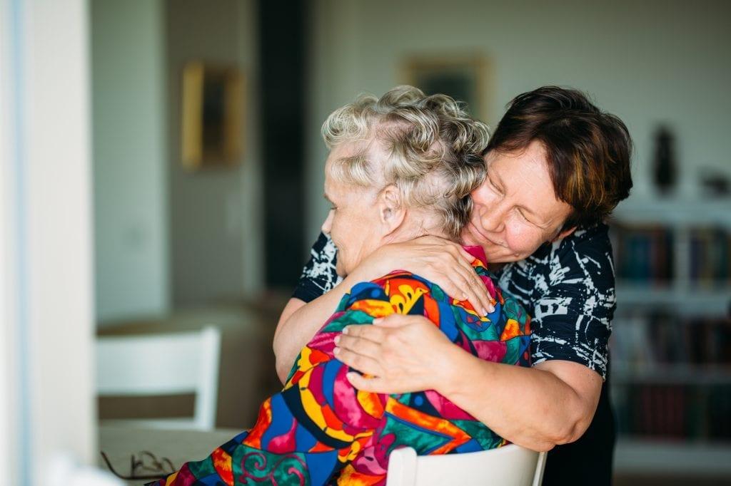Hoitaja halaa vanhaa naista.