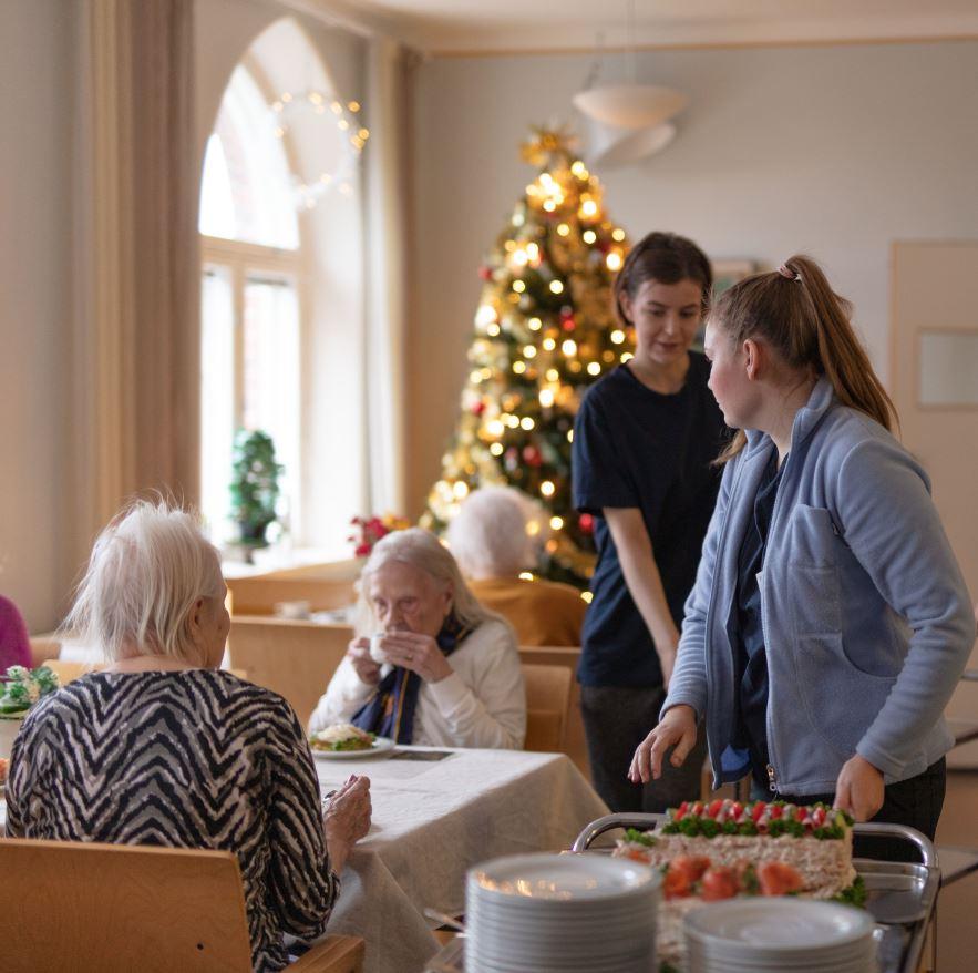 Kaksi naista tarjoaa kahvia ja kaksi vanhempaa naista istuu pöydän ääressä juomassa kahvia. Taustalla joulukuusi. Paikka on hoivakoti Scilla.