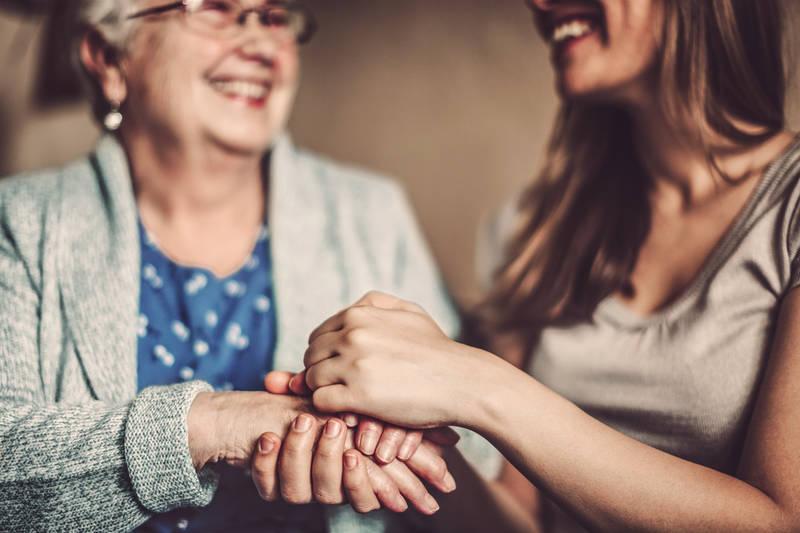 Kaksi naista pitää toisiaan kädestä. Kuvaa Hoiva Oy:n toiminta-ajatusta Ketään ei jätetä yksin.