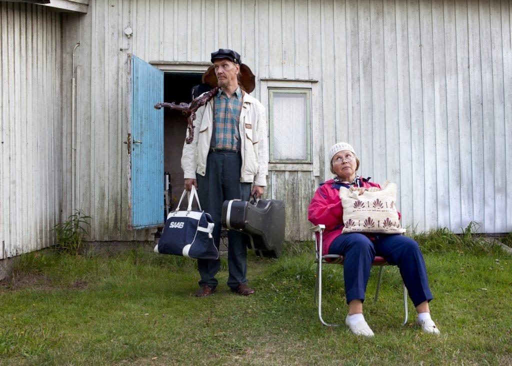 Mies seisoo matkalaukut kädessä ja nainen istuu kassi sylissään pihalla.