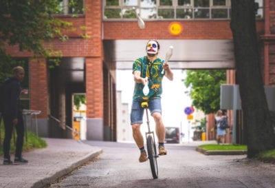 Mies jonglööraa yksipyöräisellä.