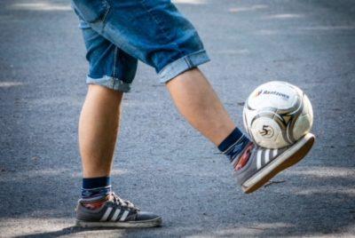Mies tasapainottelee jalkapalloa jalallaan.