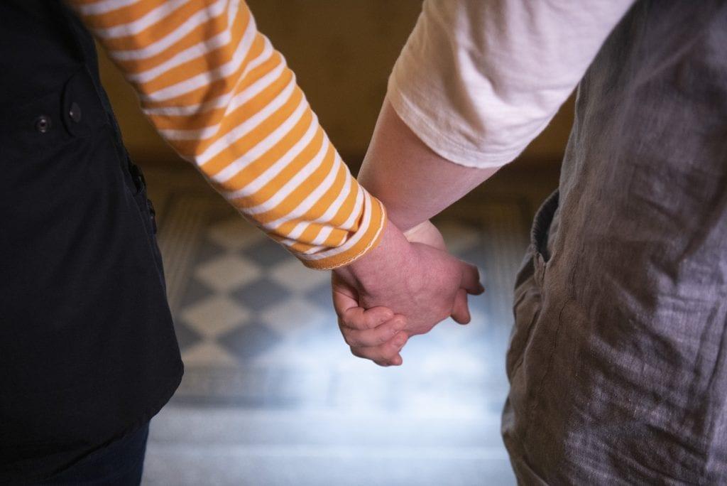 Kaksi ihmistä pitää toisiaan kädestä.