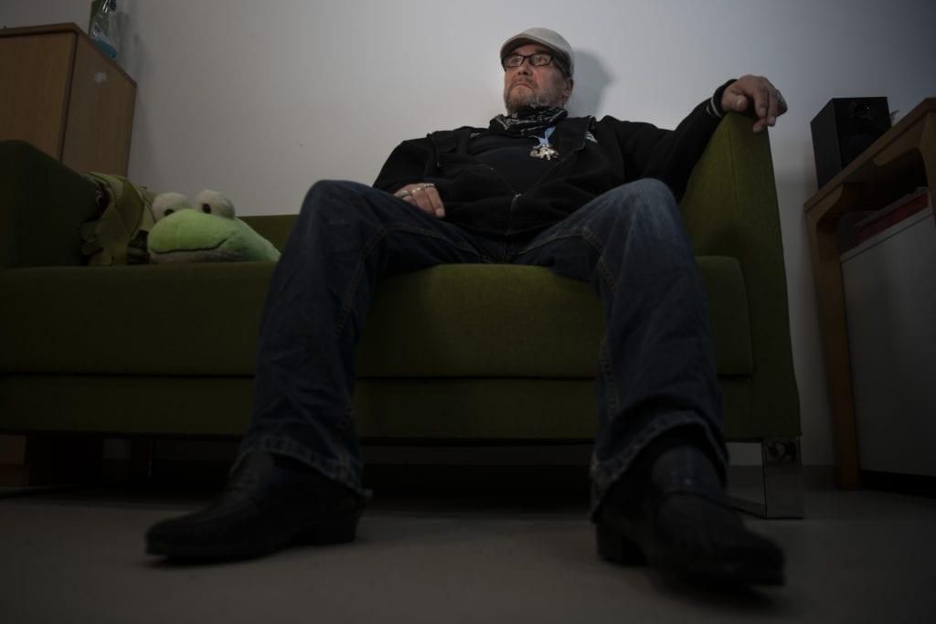 Mies istuu sohvalla
