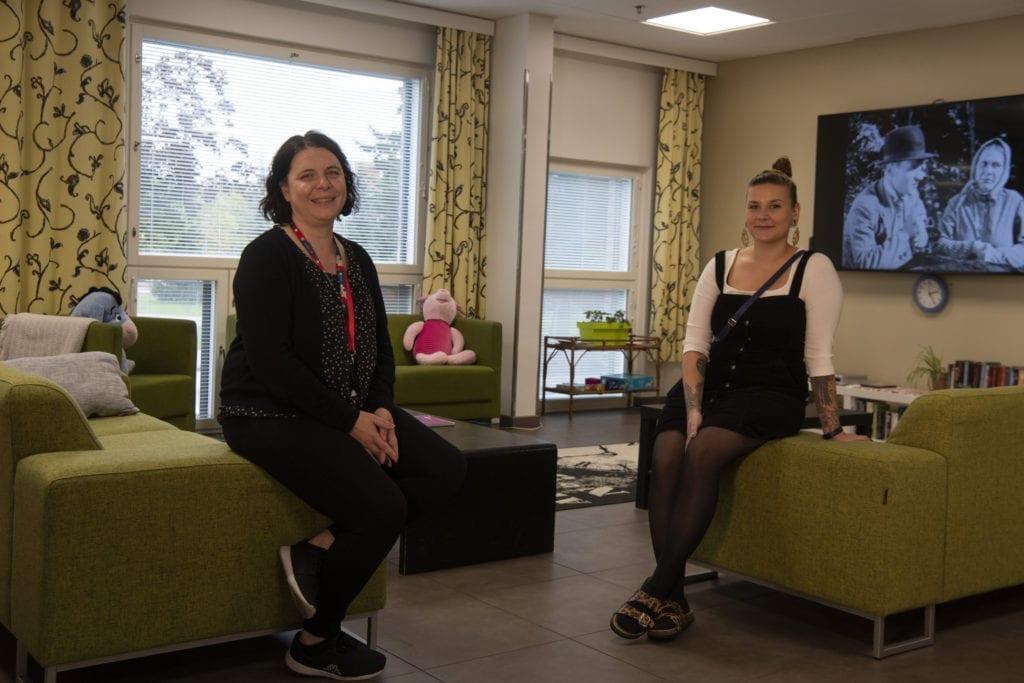 Kaksi naista istuvat sohvan reunalla