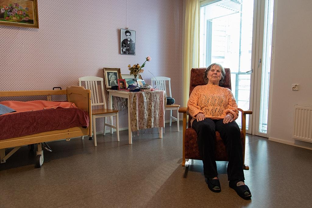 Nainen istuu keinutuolissa.