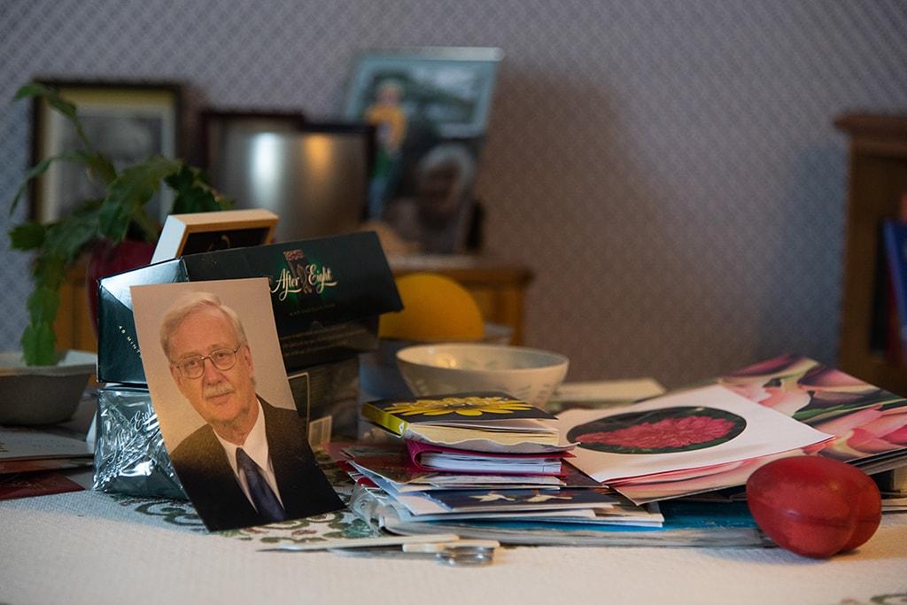 Pöydällä on kortteja ja miehen valokuva.