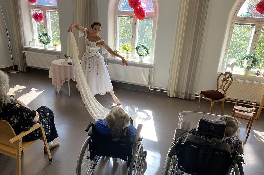 Balettitanssija esiintyy valkoisessa puvussa, katsomossa ihmisiä pyörätuoleissa.