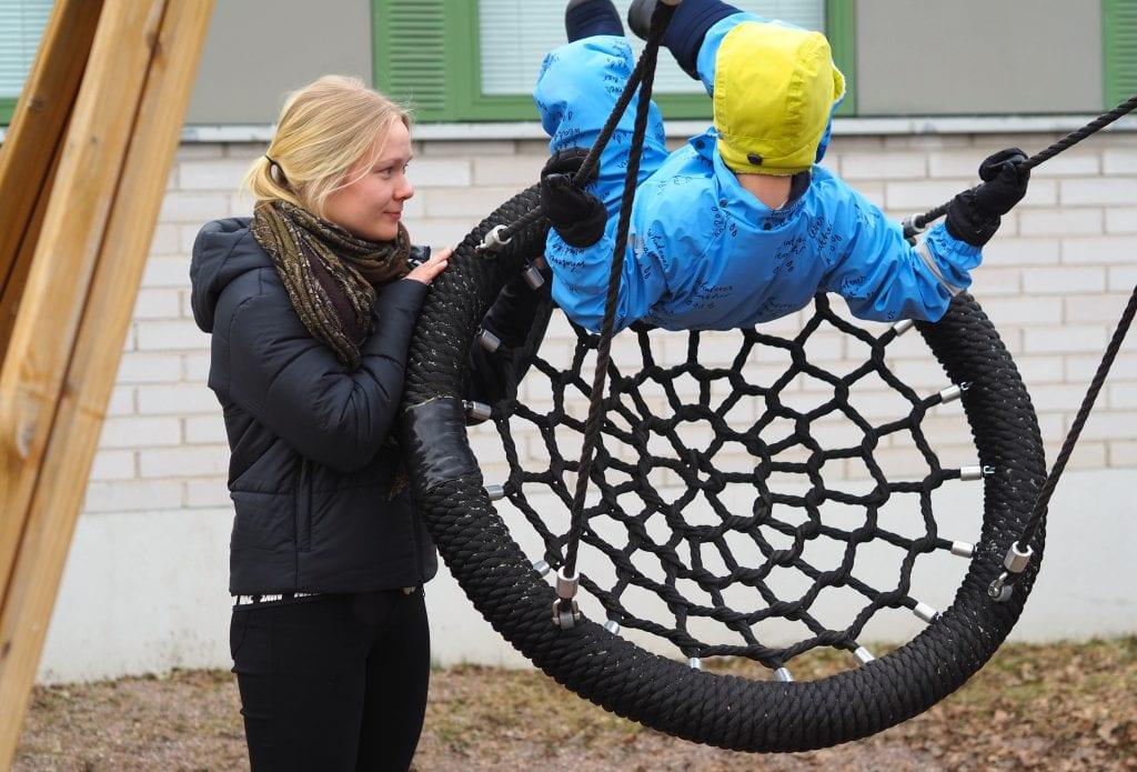 Ohjaaja ja lapsi ulkona hämähäkkikeinussa