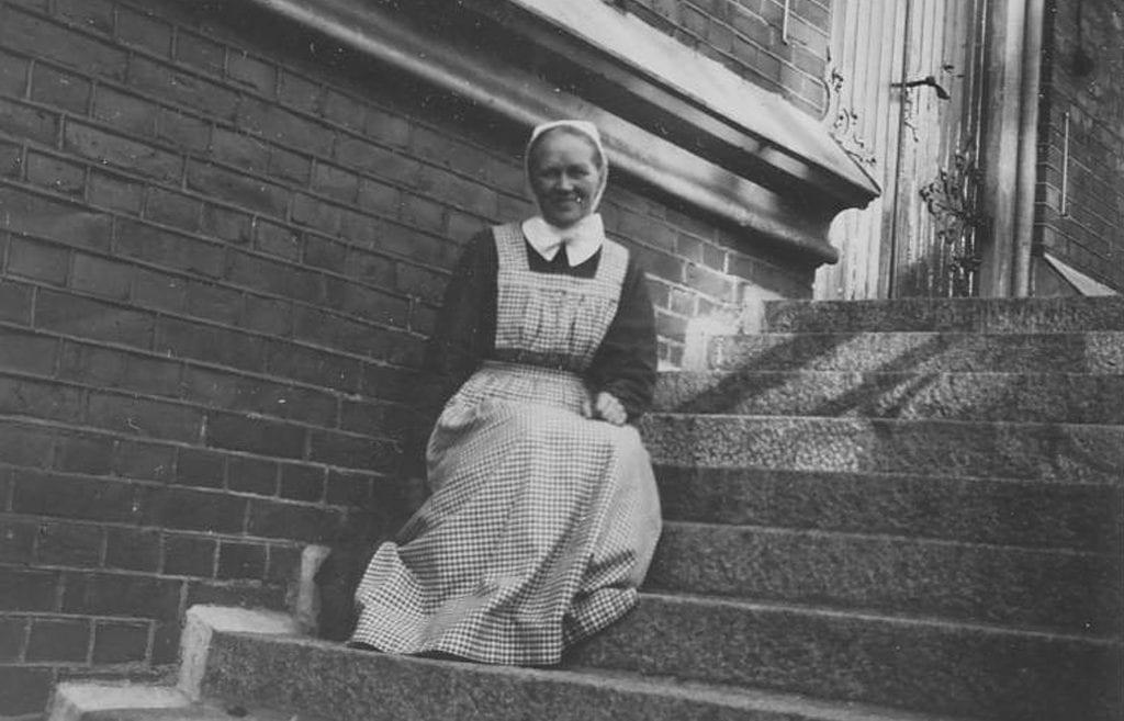 Sisar Aino Miettinen istuu Diakonissalaitoksen kirkon portailla.