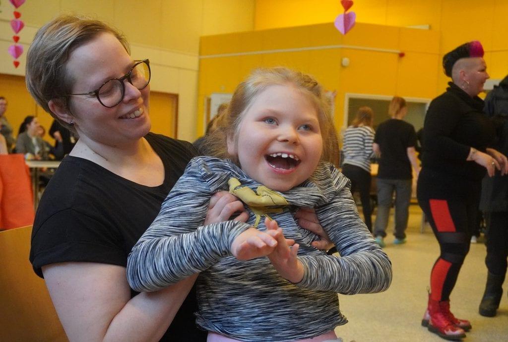 Lapsi ja hoitaja iloitsevat Care Day juhlassa