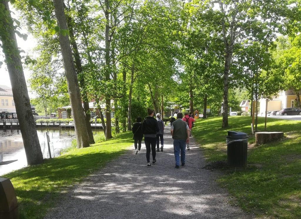 Kattaran henkilökuntaa ja asiakkaita ulkoilemassa vehreässä puistossa