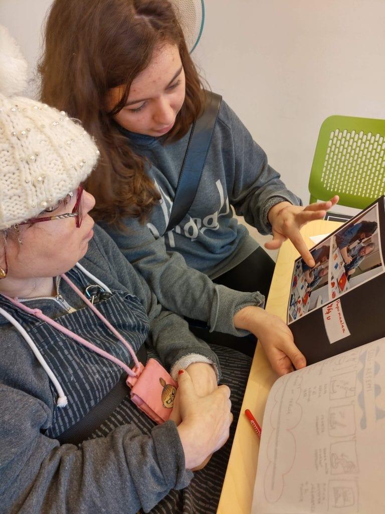 Kaksi naishenkilöä katsovat kuva-albumista kuvia.
