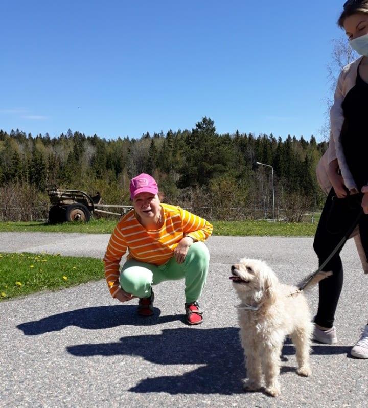 Nainen kyykistyneenä ulkona ihailemaan hihnassa olevaa valkoista koiraa