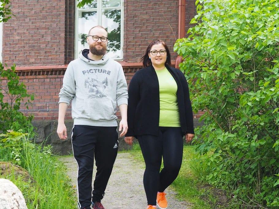 Joppe ja Mira kävelevät polkua pitkin vierekkäin punaisen tiilirakennuksen edessä.