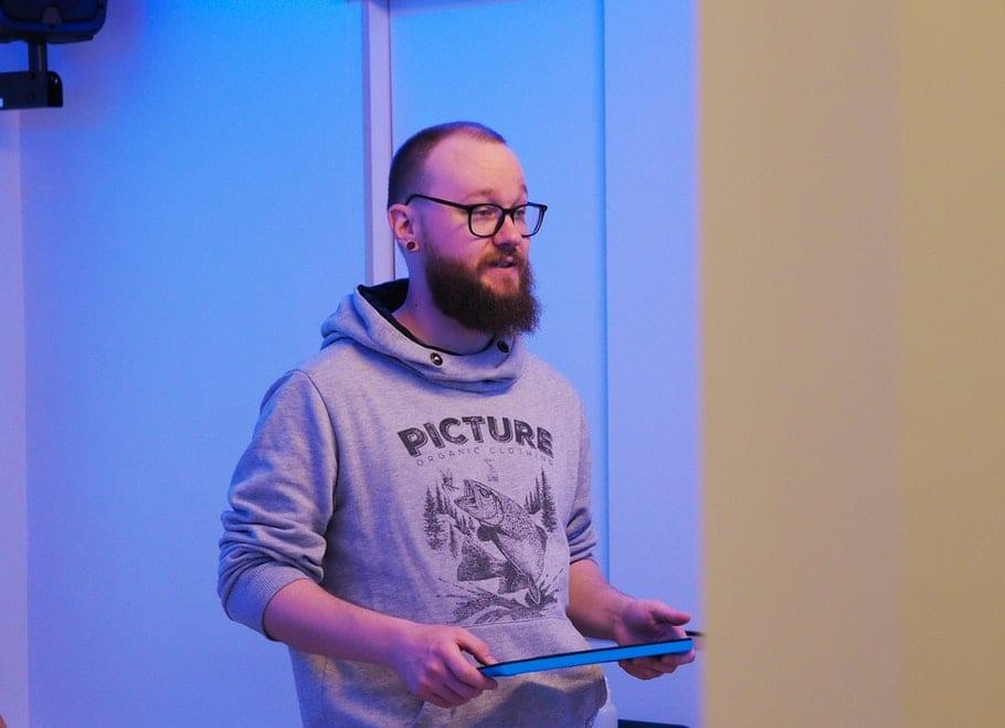 Joppe seisoo sinisensävyisessä huoneessa tabletti kädessään.