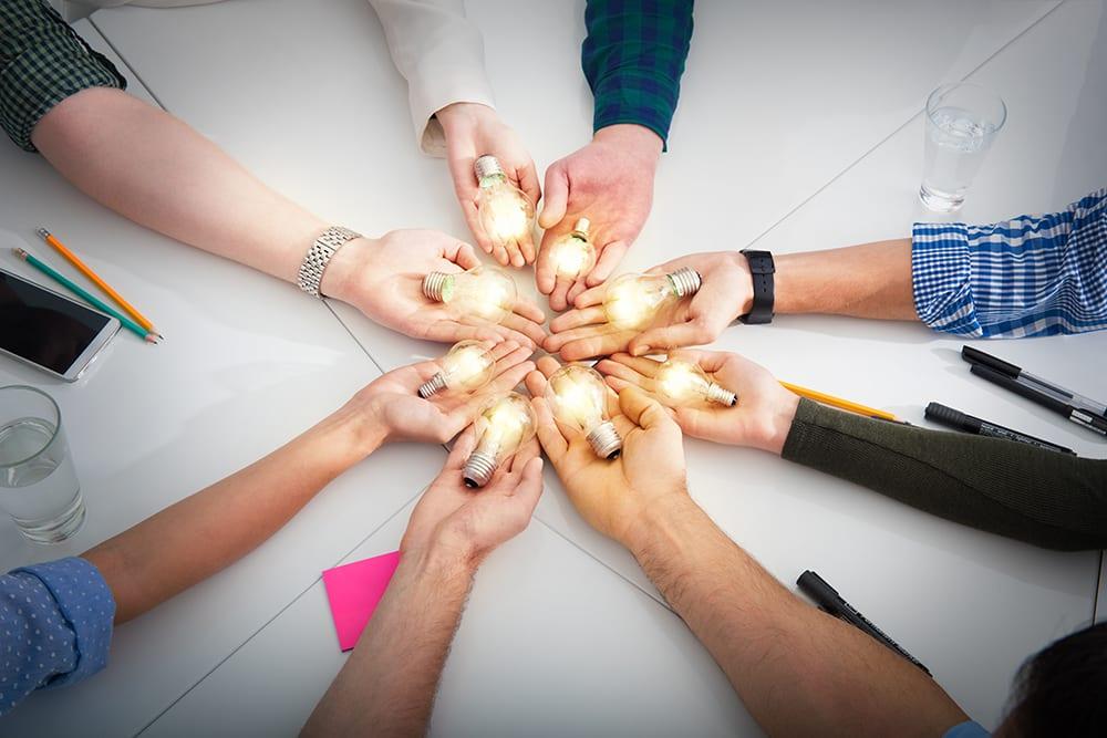 Kahdeksan kättä ringissä pitävät kukin kämmenessään hehkulamppua, jossa valo päällä.