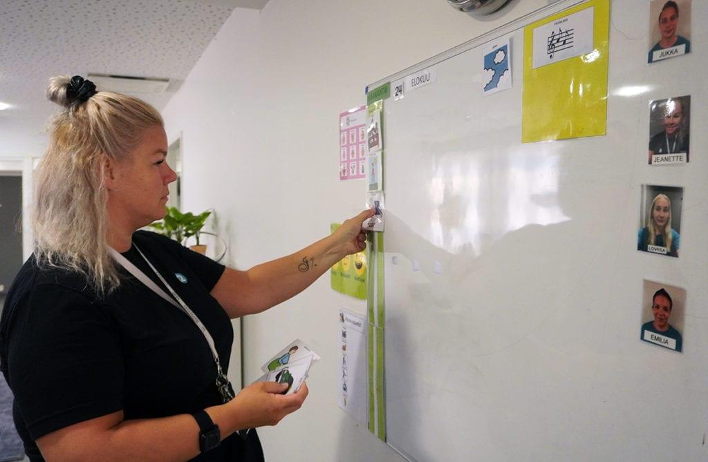 Jeannette Auvinen asettaa päiväohjelmakuvia valkotaululle.