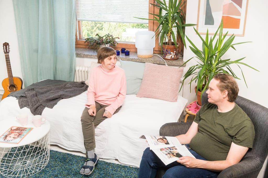 Kuva kotoa. Nainen istuu sängyllä hymyillen. Mies istuu nojatuolilla selaillen aikakausilehteä.