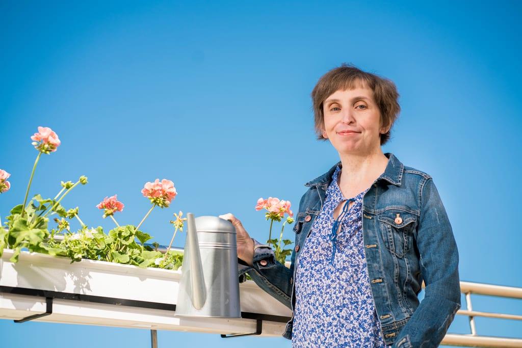 Nainen seisoo parvekkeella kukkien edessä ja pitää kastelukannua kädessä. Taustalla kirkkaansininen taivas.