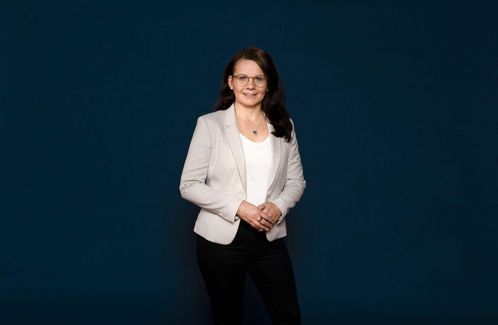 Jaana Laaksonen seisoo tummansinisen seinän edustalla hymyileväisenä.