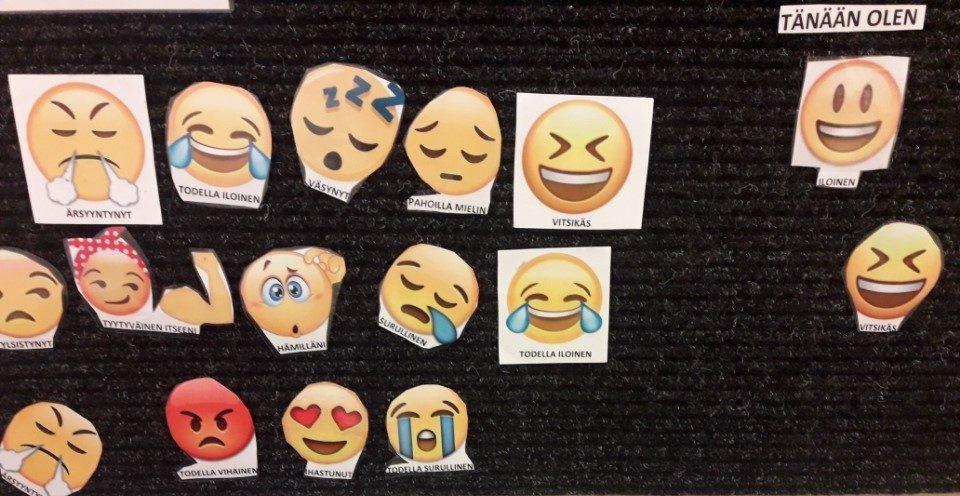 Mustalla tarraseinällä useita erilaisia keltaisia emoji-kuvia.