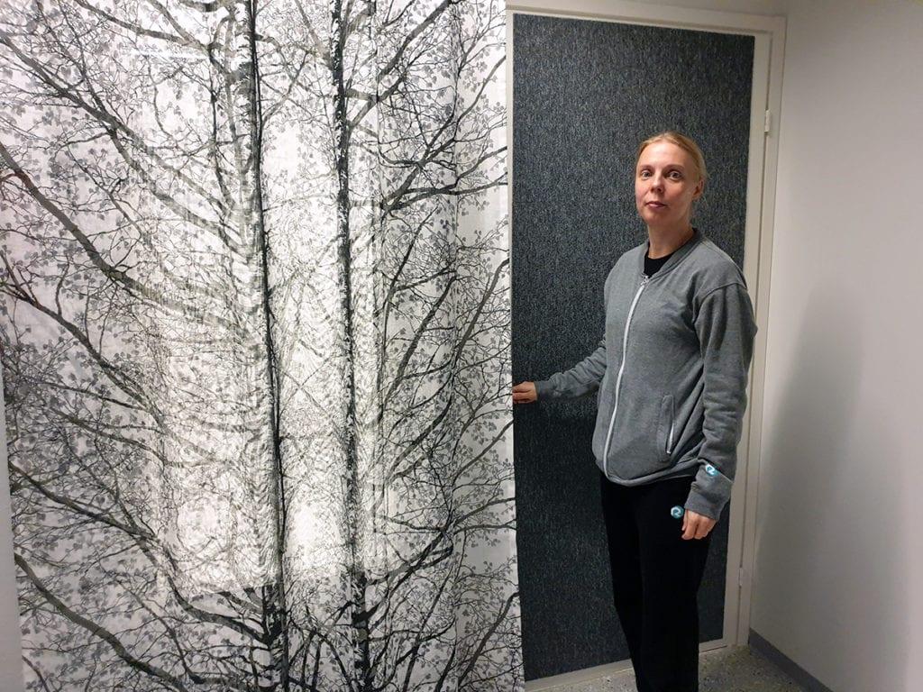Nainen seisoo harmaan oven vieressä oven kahvasta kiinni pitäen. Huoneen ikkunaa peittää iso valko-musta verho, jossa koivun kuvio.