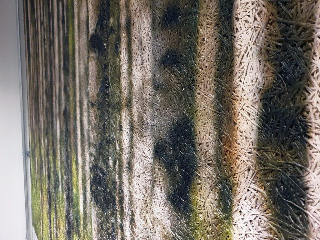 Lähikuva metsämaisemataulusta, jossa erottuu kuvan tekstuuri. Tekstuurissa punosmaista kuviointia.