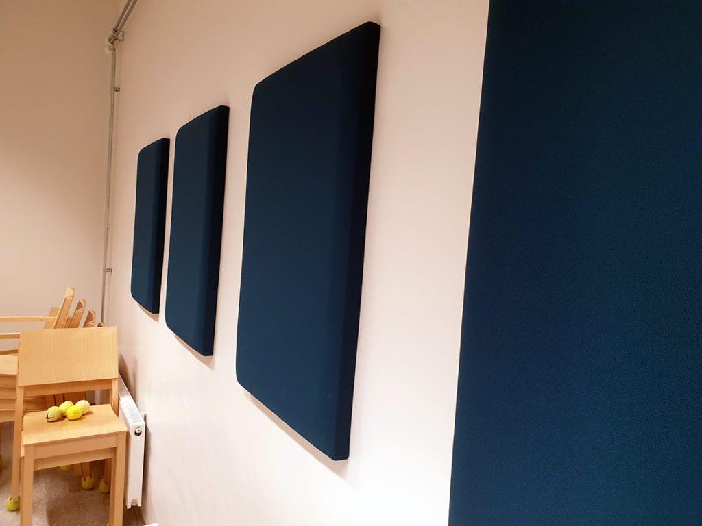 Neljä tummansinistä akustiikkataulua kiinnitettynä valkoiseen seinään.