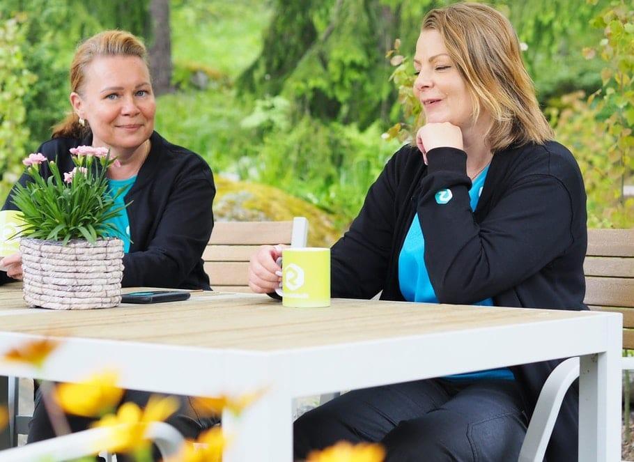 Kaksi naista istuu ulkona terassipöydän äärellä ja pitävät kahvikuppeja käsissään.