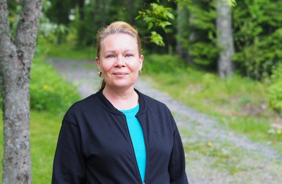 Mustatakkinen nainen seisoo metsäpolun varrella ja katsoo kameraan päin hymyillen.