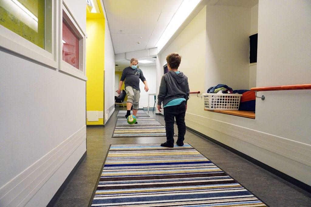 Alueohjaaja potkii nuoren kanssa jalkapalloa pitkällä käytävällä.