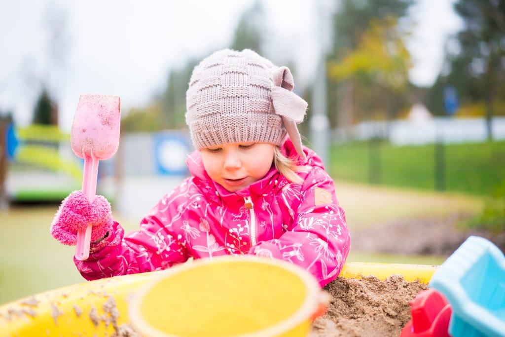 Pieni tyttö leikkii leikkipuistossa hiekkalaatikolla lapio kädessään.
