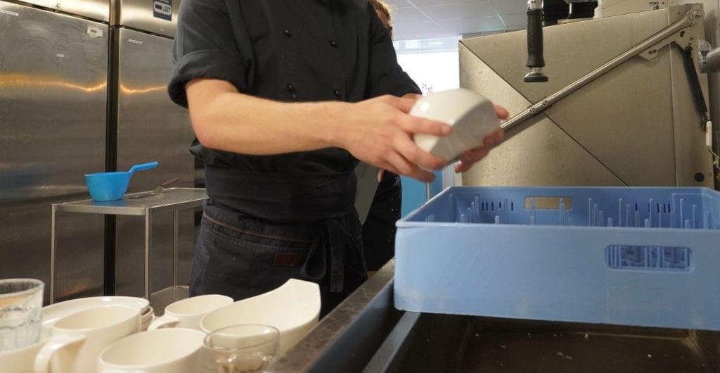 Mustapaitainen henkilö asettaa tiskejä tiskiin keittiössä.