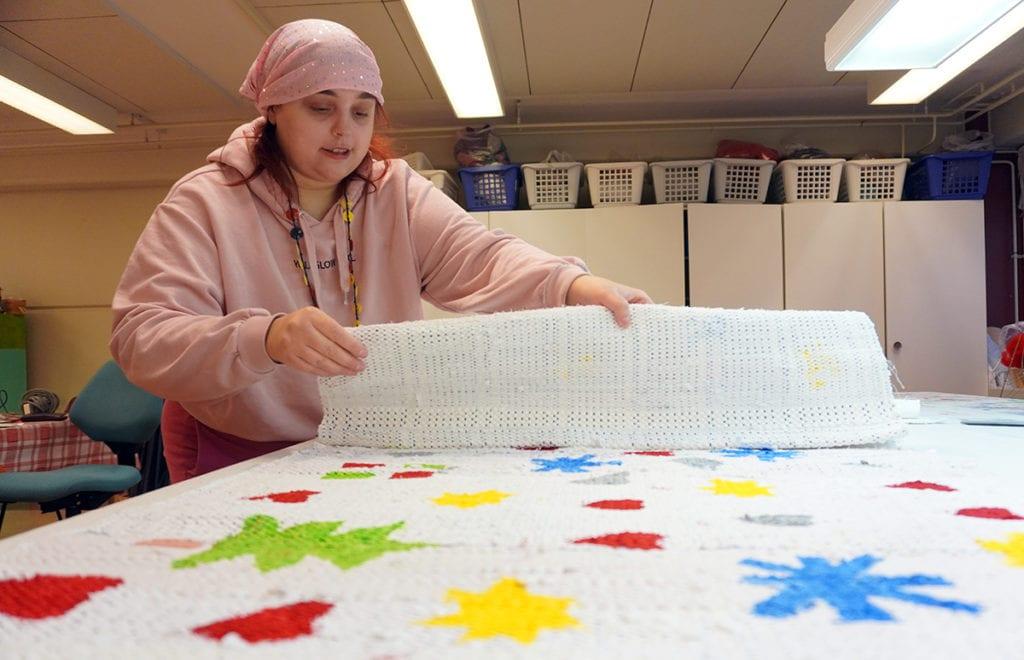Henkilö viikkaa valkoista käsityöteosta, jossa on punaisia, sinisiä, keltaisia ja vihreitä jouluisia kuvioita.