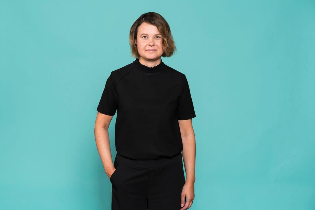 Anna Eskola seisoo turkoosin seinän edustalla.
