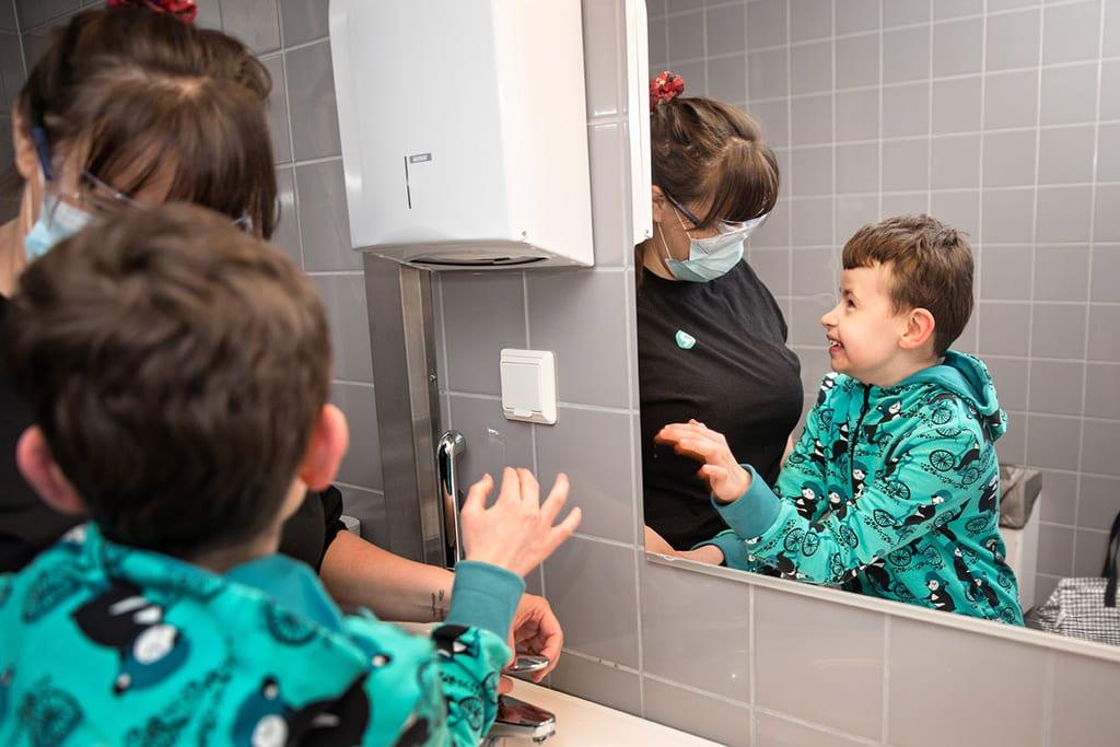 Aikuinen ja lapsi pesevät käsiä kylpyhuoneessa.
