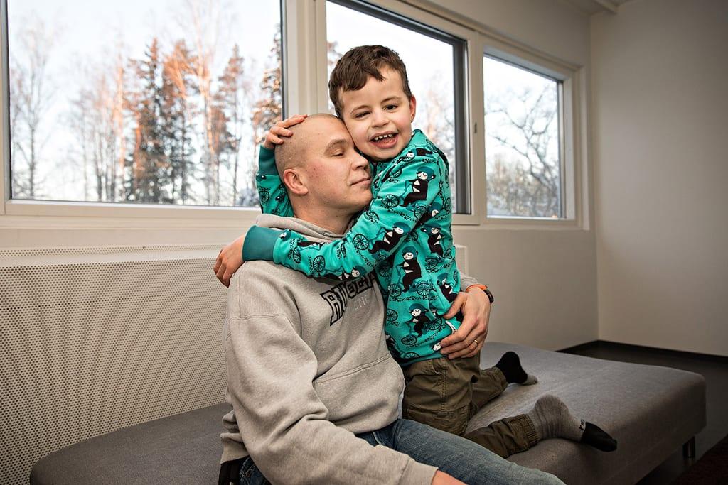 Mies ja lapsi halaavat.