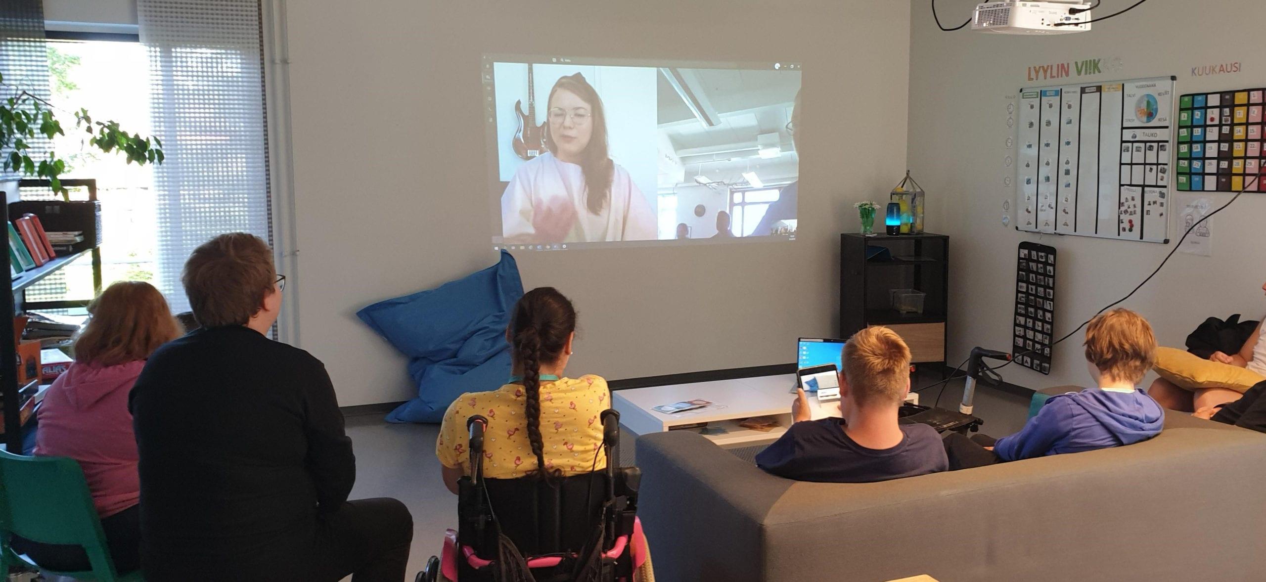 Henkilöitä istumassa sohvalla ja katsomassa seinälle heijastettua videota.
