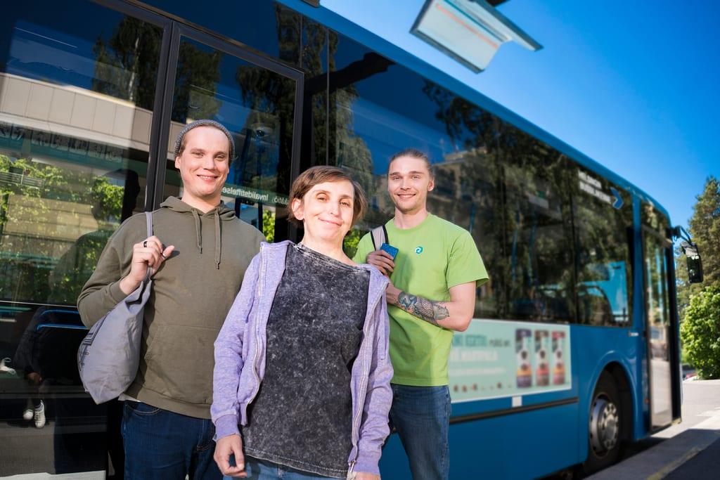 Kolme henkilöä seisoo bussin edustalla.